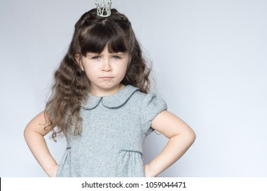 Capricious child. Spoiled little girl with crown on head, her hands on her hips