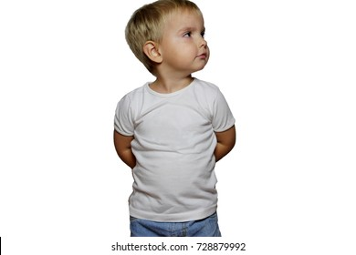 Capricious little blond boy in white T-shirt over white background, hands behind the back, isolated, sign and gesture concept, close-up emotion portrait