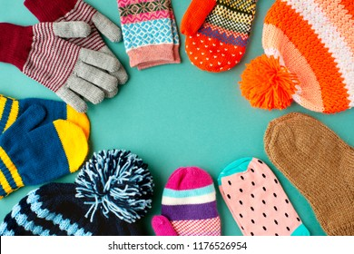 Caps, mittens, gloves and socks are stacked in a circle. View from above. Warm clothes in the form of hats, mittens, gloves and socks for autumn and winter. Warm clothes for cold seasons.
