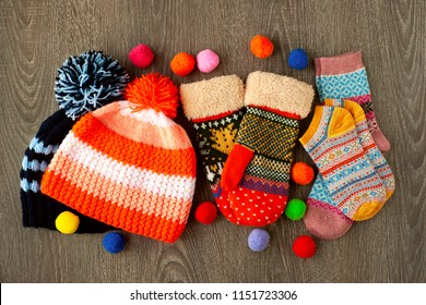 Caps, mittens and socks for cold seasons. Warm clothes in the form of knitted hats, colorful mittens and socks on a wooden background. Clothes for autumn and winter.