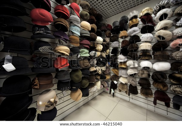 Caps, winter caps, hats, berets and other headdress on wall in shop