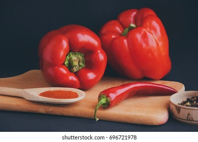 Capsicum,red bell pepper, chili pepper and alispice on the black background and wooden backround. Picture of all types of pepper.