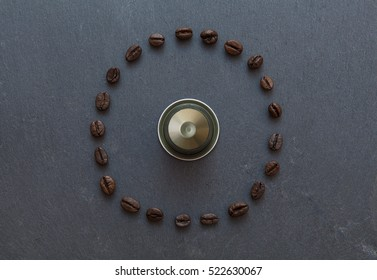 Capsule of coffee Nespresso from top view with coffee beans all around in circle, on gray stone, selected focus on beans