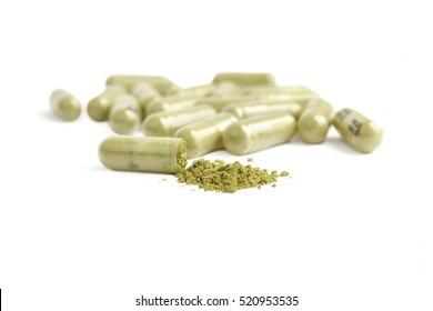 capsule with green pills on white background