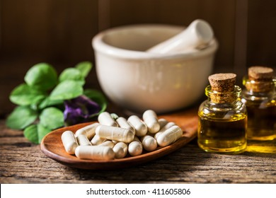 capsule pill with herb, essential oil and ceramic mortar on wooden background for alternative medical concept.