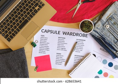 Capsule wardrobe concept. Clothes, laptop and color palette on wooden desk. Flat lay