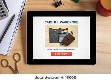 Capsule wardrobe concept on tablet screen with office objects on wooden desk. All screen content is designed by me. Top view