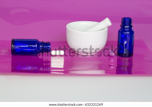 Capsules in blue glass bottles on pink background