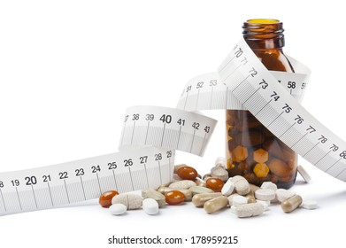 capsules for diet with pills bottle and tape meter on white background