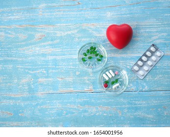 Capsules or druga or pill and rubber hearts are on the wooden table.