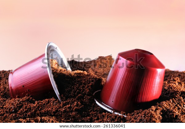 capsules for espresso coffee machine on heap of ground coffee and brown isolated background