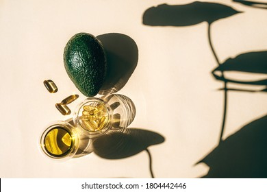 Capsules fish oil omega-3 in glass cups and an avocado with a shadow of monstera leaves in the sunlight on the beige background. Health and beauty concept.