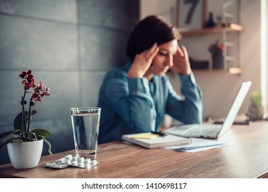 Capsules and glass of water on office desk and woman with a headache in the background holding hand on a head