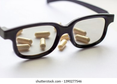 Capsules with glasses on light background. Pharmacy and medicine concept. Focused on a pharmaceutical industry for eye diseases. Selective focus photography