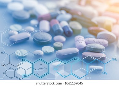 A lot of capsules and tablets on the table with chemical hud graphic The medicines  are good treatment if order from the doctor.  Pills is dangerous when take overdose