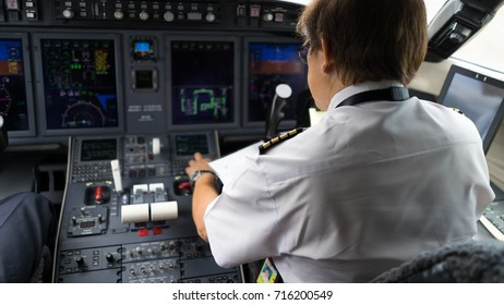 Captain in the aircraft cockpit, preparing for flight departure. Focusing on his pilot epaulets.