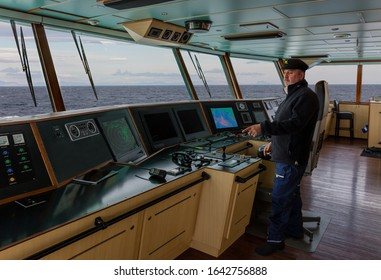 The captain with a beard and a blue cap stands on the bridge of a cargo ship and points to the handheld radio. Through the windows you can see the sea and mountains on the horizon.