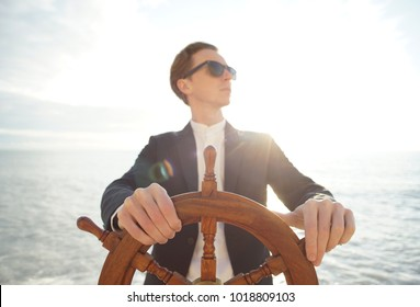 Captain. Businessman holding hand on ship rudder.