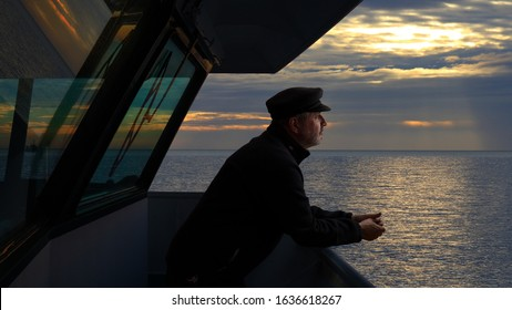 The captain of a cargo ship looks with satisfaction on the bridge towards the Mediterranean. It is an evening in February and the sun is low behind the clouds. Reflections on the water.