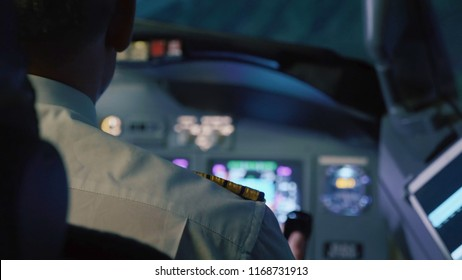 Captain is controls the airplane at night, rear view. Pilot in cockpit of passenger airliner.