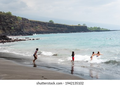 CAPTAIN COOK, HI, U.S.A. - DEC. 31, 2020:  African-American and Caucasian young women have fun in the ocean at Hookena Beach Park.  The beach has grey-sand with a canoe fishing history.