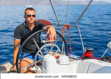 Captain at the helm controls of a sailing boat during sea yacht race.