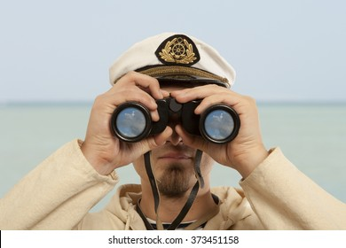 Captain looks through a binoculars. Marine concept