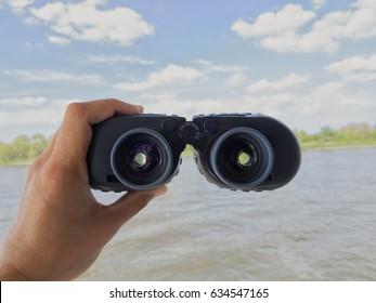 Captain man hand binoculars on a beautiful day on the rhine river, binoculars sailor,verrekijker binnenvaart
