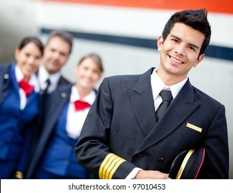 Captain pilot with cabin crew and an airplane at the background