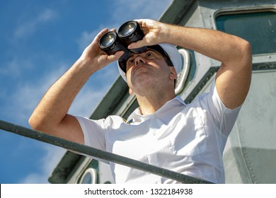 Captain of ship looking ahead. A sailor officer in white uniform looking to sea with binocular aboard a ship.