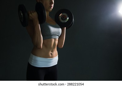 Caption of fit womans upper body wearing training clothes lifting two weights up