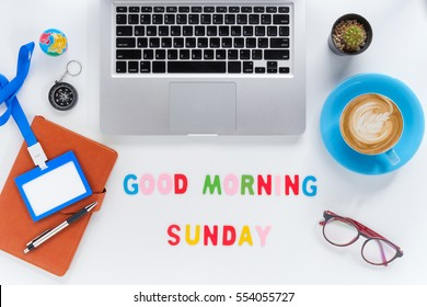 Caption word  Good morning sunday. White office desk with laptop, diary, eyeglasses, compass, pen, blank identification card and cup of coffee on white background.