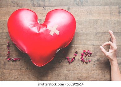 Caption word LOVE with red broken heart with bandage, dried rose petals and hand sign OK. Broken heart concept on wood floor