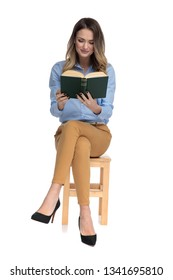 captivated smart casual woman reading while sitting