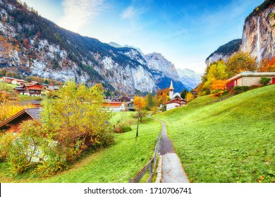 Captivating autumn view of Lauterbrunnen valley with gorgeous Staubbach waterfall and Swiss Alps in the background.  Location: Lauterbrunnen village, Berner Oberland, Switzerland, Europe.