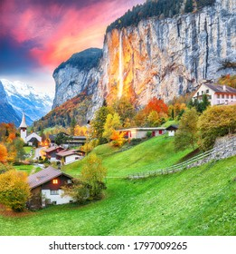 Captivating autumn view of Lauterbrunnen valley with gorgeous Staubbach waterfall and Swiss Alps at sunset time.  Location: Lauterbrunnen village, Berner Oberland, Switzerland, Europe.