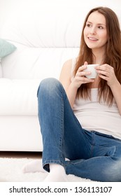 Captivating woman holding a cup sitting on the floor at home