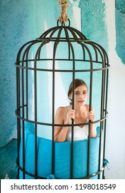 captive in fear. modern furniture design and home comfort. fashion slave in captivity of beauty. woman inside iron cage. freedom of cute girl in cage chair. prisoner woman in cage - home confinement.