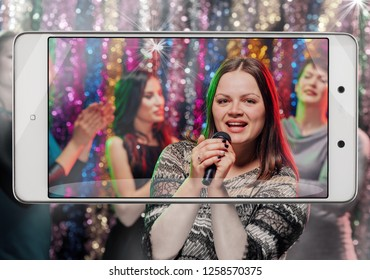 Capture the moment of happy pretty woman singing at night party, smart device concept