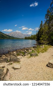 I captured this image while hiking around Leigh Lake in Grand Teton National Park in Wyoming. Mountains are distant. Blue sky is reflected in the  water. Forests and sand surround the lake.