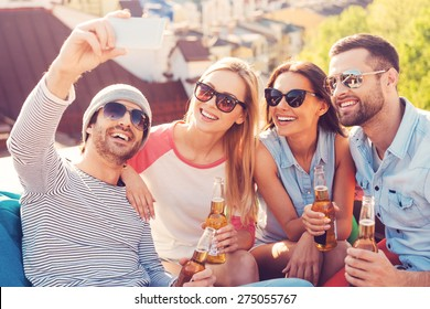 Capturing fun. Four young cheerful people making selfie and smiling while sitting at the bean bags on the roof of the building