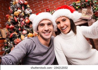 Capturing a happy moment. Beautiful young loving couple bonding to each other and smiling while making selfie with Christmas Tree in the background