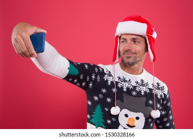 Capturing a happy moment. selsie time. time to celebrate new year. happy holidays. greeting family online. man santa claus hat. make photo on holiday party. man make selfie on phone. best wishes.