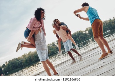 Capturing happy moments. Beautiful young couples spending carefree time while standing on the pier