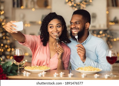 Capturing Moments. Beautiful lovely young african american couple taking selfie while sitting at table and having dinner. Smiling woman and man eating pasta and having fun at restaurant or at home