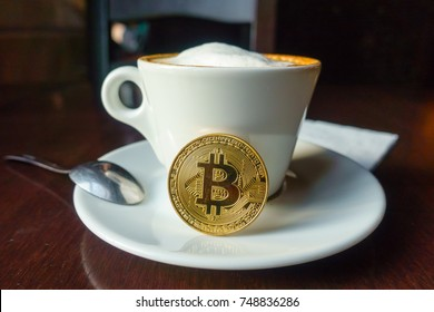 Capuccino and bitcoin gold coin on the table in cafe. Payment by crypto currency concept