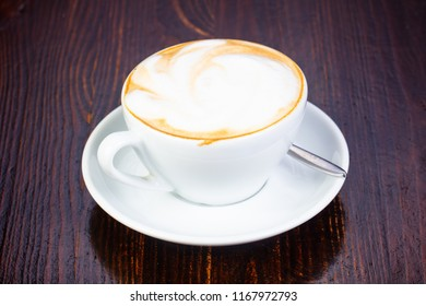 Capuccino coffee cup over wooden background