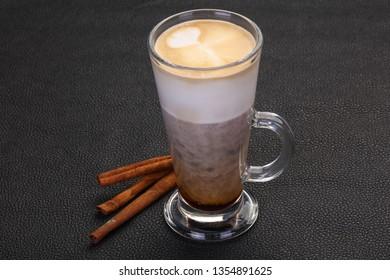 Capuccino in the glass served cinnamon sticks