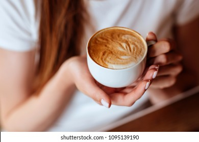 capuccino in hands of young girl in cafe
