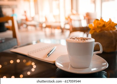 Capuccino, mocha, latte,americano, espresso hot coffee aroma in cup breakfast morning drink on wooden table vintage bar windows in cafe shop with newspaper restaurant background,copy space the left.